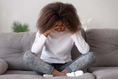 Depressed upset african american teen child girl feeling hurt sitting alone